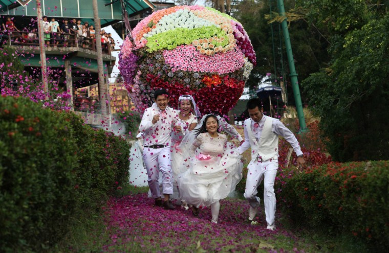 Thai grooms and their brides (L-R) Sorawich Changtor, 28, Rungnapa Panla, 30, Varuttaon Rangsiyawong, 27, and Prasit Rangsiyawong, 29, run during a wedding ceremony ahead of Valentine's Day in Prachin Buri province, east of Bangkok. Three Thai couples took part in the wedding ceremony arranged by a Thai resort, aimed to strengthen the relationships of the couples by doing fun activities. (Kerek Wongsa/Reuters)
