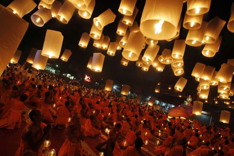 Buddhist monks release paper lanterns into the sky in Suphan Buri province, Thailand, on January 9, 2013. The lanterns were released during a traditional pilgrimage to pay homage to Lord Buddha and bless Thailand as it enters the new year. (Sukree Sukplang/Reuters)