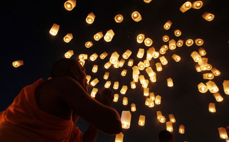 A Buddhist monk prays as he looks at paper lanterns into the sky in Suphan Buri province, Thailand, on January 9, 2013. The lanterns were released during a traditional pilgrimage to pay homage to Lord Buddha and bless Thailand as it enters the new year. (Sukree Sukplang/Reuters)