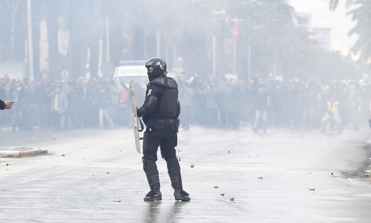 A riot police officer faces off with protesters during a demonstration in Tunis. Tunisian police fired teargas to disperse protesters demonstrating in the capital outside the Interior Ministry against the killing of a prominent secular opposition politician on Wednesday, witnesses said. (Zoubeir Souissi/Reuters)