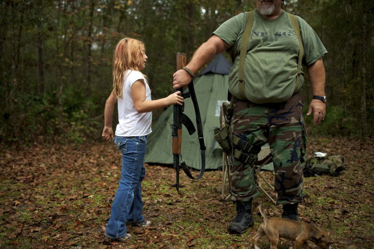 Brianna, 9, of the North Florida Survival Group hands an AK-47 rifle to Jim Foster, 57, the group's leader, before heading out to conduct enemy contact drills during a field training exercise in Old Town, Florida, December 8, 2012. (Brian Blanco/Reuters)