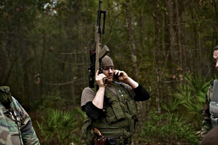 A member of the North Florida Survival Group takes a break from performing an enemy contact drill to call his wife during a field training exercise in Old Town, Florida, December 8, 2012. (Brian Blanco/Reuters)