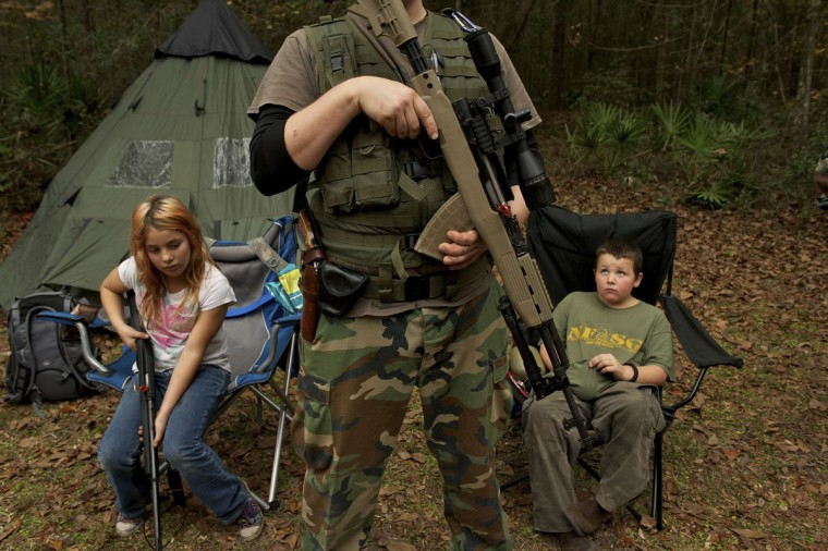 Member of the North Florida Survival Group wait with their rifles before heading out to perform enemy contact drills in Old Town