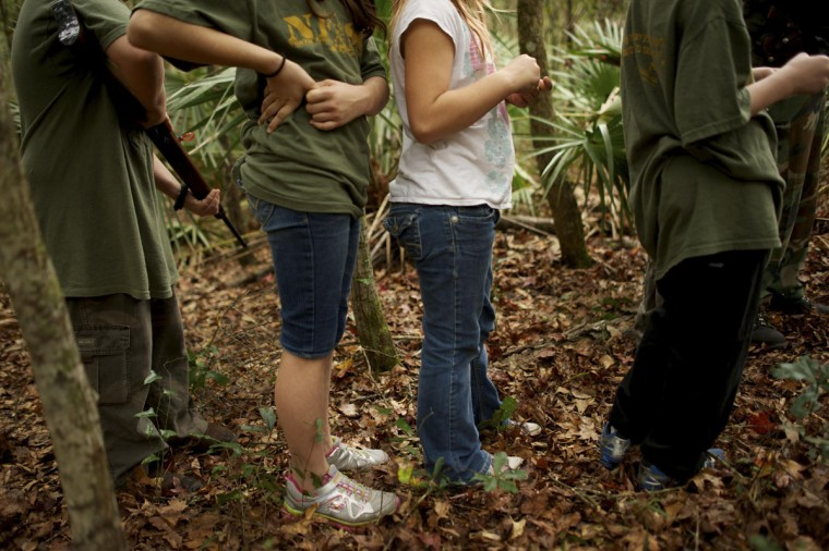 A group of children, all members of the North Florida Survival Group, walk through a wooded area during a field training exercise in Old Town, Florida, December 8, 2012. (Brian Blanco/Reuters)