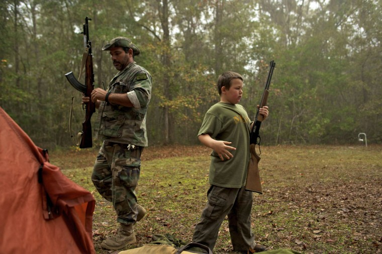 A member of the North Florida Survival Group and his young son gather their rifles before heading out to perform land navigation and enemy contact drills during a field training exercise in Old Town, Florida, December 8, 2012. (Brian Blanco/Reuters)
