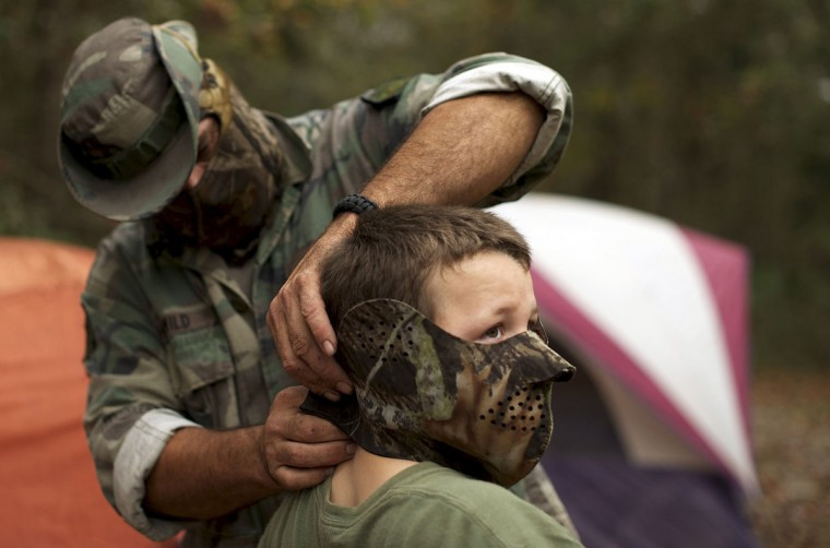 A member of the North Florida Survival Group puts a mask on his son as they gear up to perform enemy contact drills in a wooded area during a field training exercise in Old Town, Florida, December 8, 2012. (Brian Blanco/Reuters)