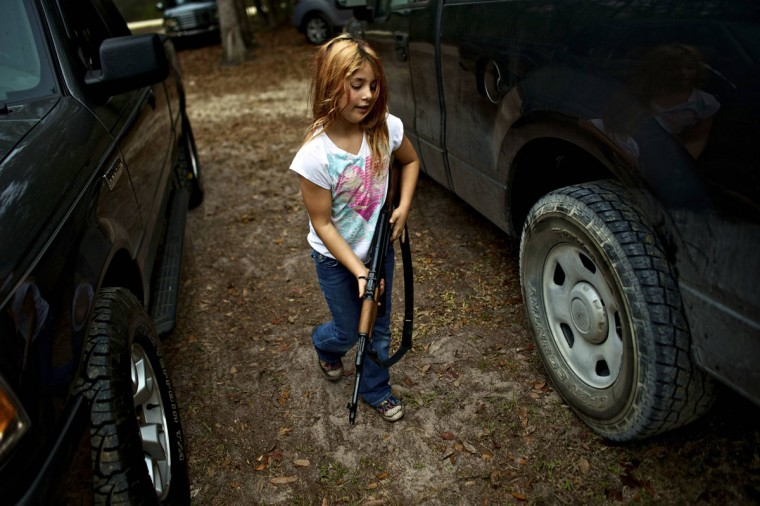 Brianna, 9, of the North Florida Survival Group carries an AK-47 rifle from the group leader's truck before heading out to conduct enemy contact drills during a field training exercise in Old Town, Florida, December 8, 2012. (Brian Blanco/Reuters)