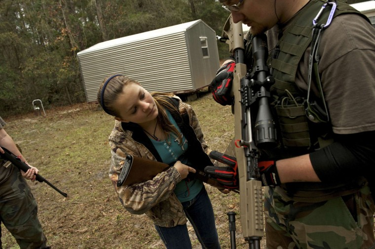 A member of the North Florida Survival Group shows the daughter of another member how to operate the magazine release of an SKS rifle during a field training exercise in Old Town, Florida, December 8, 2012. (Brian Blanco/Reuters)