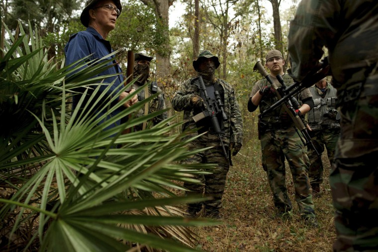 Members of the North Florida Survival Group listen as their leader critiques their performance during an enemy contact drill training exercise in Old Town, Florida, December 8, 2012. (Brian Blanco/Reuters)