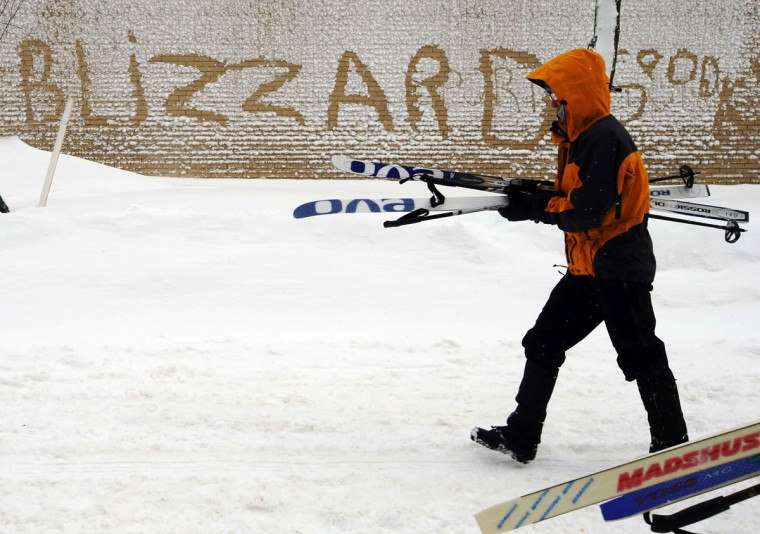"A pedestrian carries their skis past the word ""Blizzard"" written in the snow on the side of a building in Boston on Feb. 9, 2013, during a winter blizzard. (Brian Snyder/Reuters)"