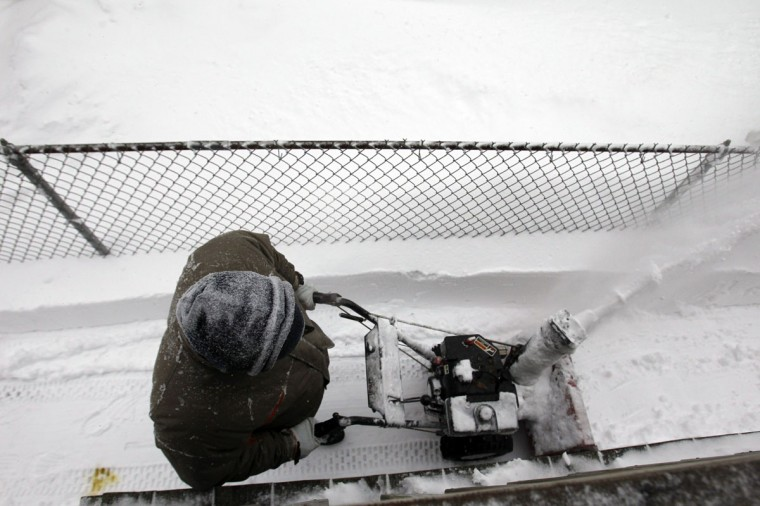 Paul Leahy uses a snowblower to clear out snow during a blizzard in Medford, Massachusetts February 9, 2013. (Jessica Rinaldi/Reuters)