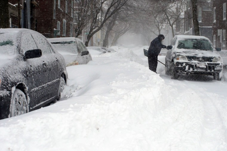 Hospital emergency room worker Susan Johnson shovels out her car to go to work during a severe winter storm in Boston, Massachusetts