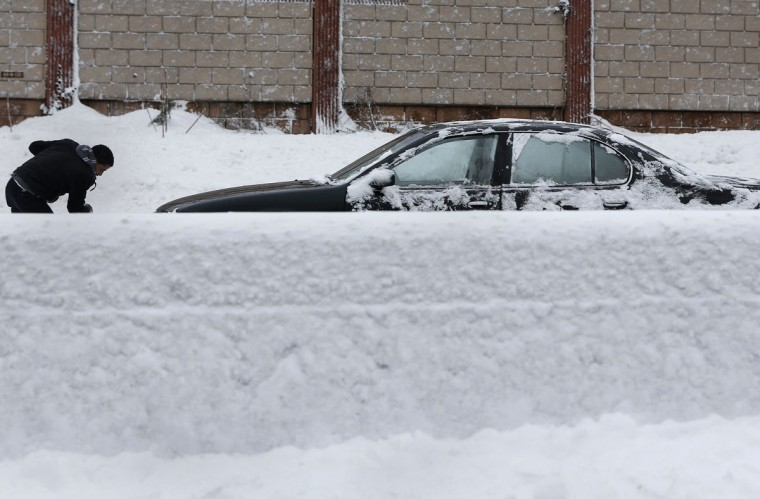 A man shovels snow from his car along the Long Island Expressway in the Suffolk County area of New York, February 9, 2013. (Shannon Stapleton / Reuters)