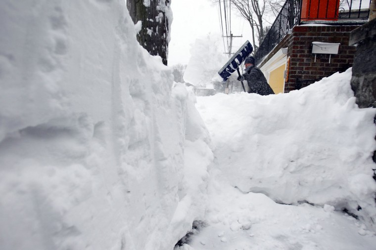 A woman works to clear snow from her sidewalk during a blizzard in Medford, Massachusetts February 9, 2013. (Jessica Rinaldi/Reuters)