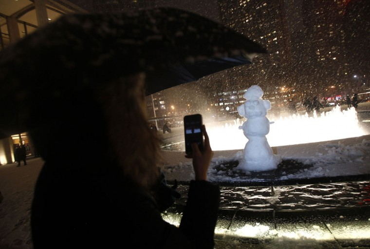 A woman takes a photo of a snow man that was erected at the fountain at Lincoln Center during New York Fashion Week in New York, February 8, 2013. A blizzard blew into the northeastern United States on Friday, cutting short the workweek for millions who feared being stranded as state officials ordered roads closed ahead of what forecasters said could be record-setting snowfall. From New York to Maine, the storm began gently, dropping a light dusting of snow, but officials urged residents to stay home, rather than risk getting stuck in deep drifts when the storm kicks up later Friday afternoon. (Carlo Allegri/Reuters Photo)
