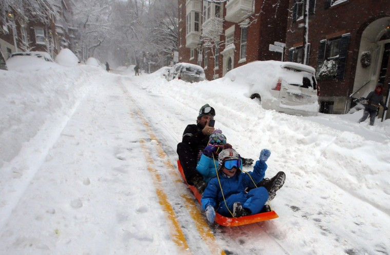 Peter Webster sleds down Chestnut Street with his children in Boston, February 9, 2013, during a winter blizzard. (Brian Snyder/Reuters)