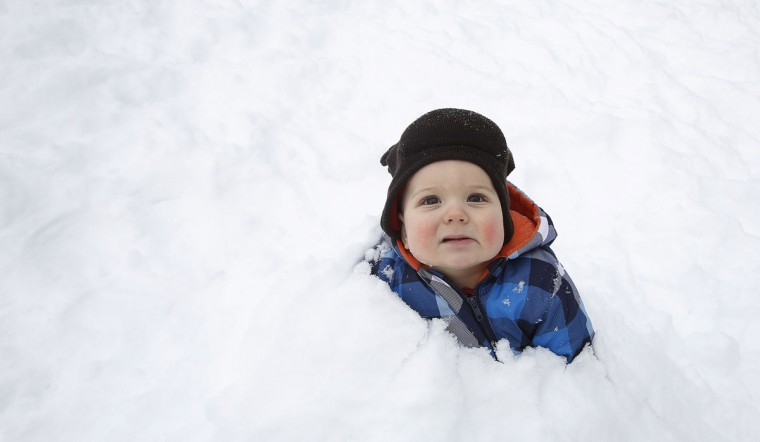 A child sits buried in the snow waiting for his father to take his photo in Central Park in New York, February 9, 2013. A blizzard pummeled the Northeastern United States, killing at least one person, leaving hundreds of thousands without power and disrupting thousands of flights, media and officials said. (Carlo Allegri/Reuters)