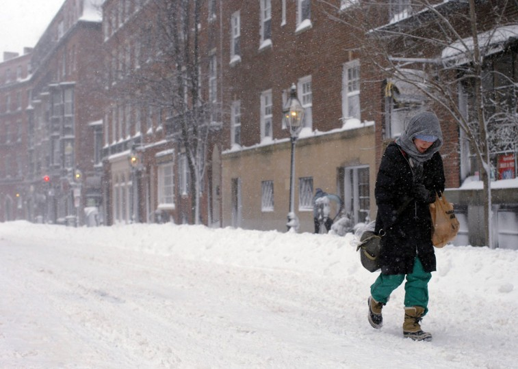 A woman walks down Charles Street during a severe winter storm in Boston, February 9, 2013. A blizzard pummeled the Northeastern United States, killing at least one person, leaving hundreds of thousands without power and disrupting thousands of flights, media and officials said.   (Brian Snyder/Reuters)