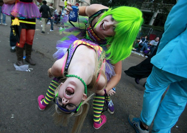 Lauren Whiddon (bottom) and Mari Wisdom dance on St. Charles Avenue as they wait for the Krewe of Bacchus parade in New Orleans, Louisiana February 10, 2013. (Sean Gardner/Reuters)