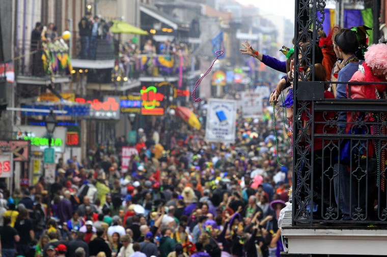Revelers throw beads off The Royal Sonesta Hotel balcony on to Bourbon Street on Mardi Gras Day in New Orleans, Louisiana February 12, 2013. (Sean Gardner/Reuters)