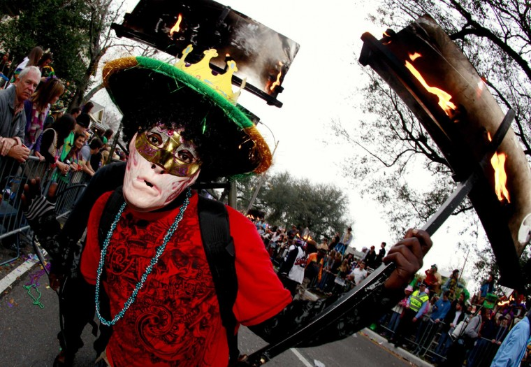 A flambeau, or flame bearer, walks along the street as members of the Krewe of Endymion parade down Orleans Avenue during the weekend before Mardi Gras in New Orleans, Louisiana February 9, 2013. (Sean Gardner/Reuters)