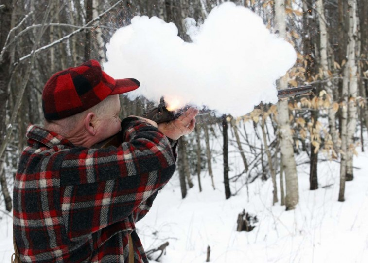 A man fires a flintlock rifle at a target as he competes in the Primitive Biathlon in Dalton, New Hampshire February 16, 2013. The Dalton Gang, a single action shooting club, holds the annual Primitive Biathlon in which competitors wear snowshoes and fire single shot muzzle loaded firearms at four stations along a 1.75 mile course. (Jessica Rinaldi/Reuters)