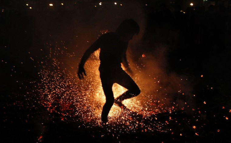 A Vietnamese man from the Pa Then minority group jumps into a fire during a ritual ceremony at the Vietnam Ethnic Minority Cultural Village, outside Hanoi. The tribe with a population of 5,000, which resides in mountainous areas bordering China, organizes the annual fire-jumping ritual for adult men at the end of the harvest season. They believe that jumping into a fire without any protection will help them gain more special energy from God to challenge life's difficulties and fight evils. (Kham/Reuters)