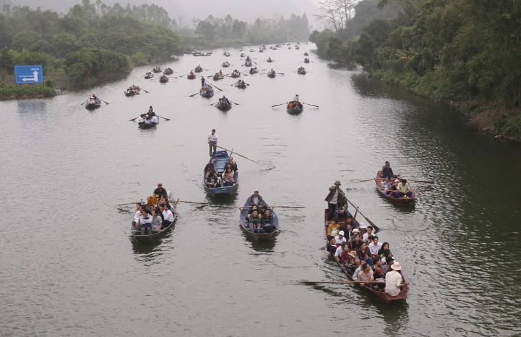 Pilgrims travel by boat on the Yen Vy river to attend the Chua Huong, or Perfume Pagoda, festival outside Hanoi. The festival is the longest and most crowded annual festival in Vietnam and lasts through three months in spring, attracting millions of pilgrims, reported local newspapers. (Kham/Reuters)