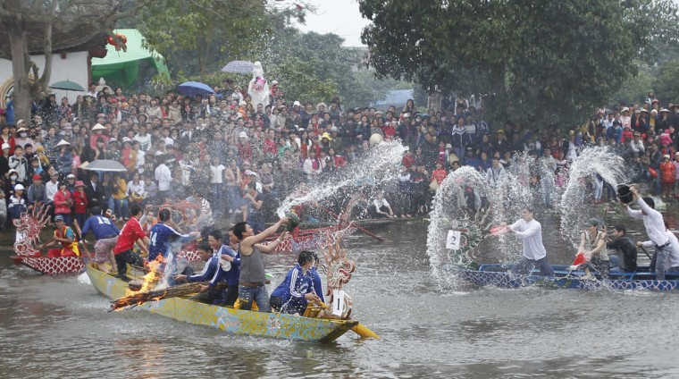Teams of villagers attempt to extinguish the fires used by their opponents to cook rice in pots on boats along a river, as part of the Bach Hao pagoda festival in Thanh Xa village, in Vietnam's northern Hai Duong province, about 80 km (50 miles) east of Hanoi. The competition was a reenactment of the training Emperor Tran Nhan Tong put 13th century villagers through to teach them to fight Chinese and Mongolia invaders on the water. (Kham/Reuters)