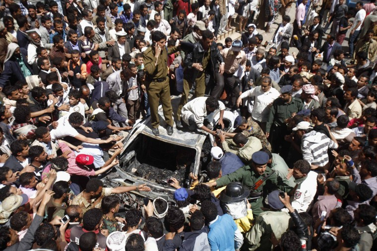 People and police officers try to recover charred bodies of the driver and passengers by cutting the wreckage of a burnt taxi at the site of a military aircraft crash in Sanaa. A Yemeni fighter jet crashed in the centre of the capital Sanaa on Tuesday, killing at least six people, medical sources said. (Khaled Abdullah/Reuters)