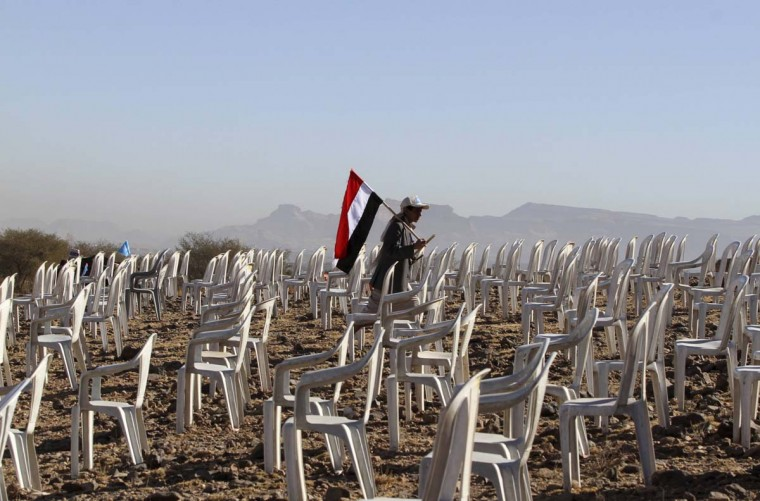 A tribesman carries a Yemen national flag as he walks between, chairs before a rally to commemorate the second anniversary of the uprising against Yemen's former President Ali Abdullah Saleh in Bani Hushaish, north of the capital Sanaa February 11, 2013. (Mohamed al-Sayaghi/Reuters)