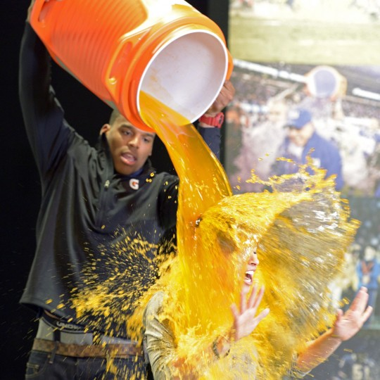 Carolina Panthers quarterback Cam Newton (left) dunks Today Show personality Jenna Wolfe with a bucket of Gatorade on radio row in preparation for Super Bowl XLVII at the New Orleans Convention Center. (John David Mercer/USA TODAY Sports)