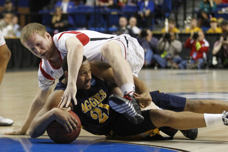 North Carolina A&T's R.J. Buck fights for a loose ball with Louisville's Tim Henderson during the second half of play in their second round NCAA basketball game in Lexington, Kentucky, March 21, 2013. (John Sommers II/Reuters)