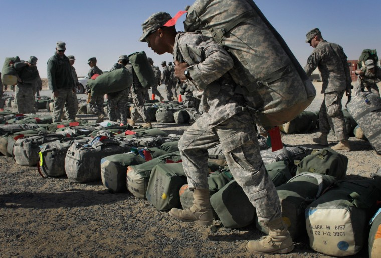 U.S. Army soldiers from 1-12, 1st Cavalry Division, carry their bags as they prepare for the flight back to Fort Hood from Kuwait after exiting from Iraq on December 13, 2011 at Camp Virginia, near Kuwait City, Kuwait. America's military continues its pullout of Iraq by the end of this year, after eight years of war and the overthrow of Saddam Hussein. (Joe Raedle/Getty Images)