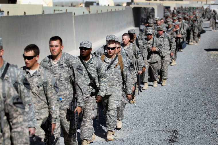 U.S. Army soldiers from the 1st Cavalry Division walk to a waiting bus as they leave customs for a ride to the airport to fly back to Fort Hood from Kuwait after exiting from Iraq on December 14, 2011 at Camp Virginia, near Kuwait City, Kuwait. America's military continues its pullout of Iraq by the end of this year, after eight years of war and the overthrow of Saddam Hussein. (Joe Raedle/Getty Images)
