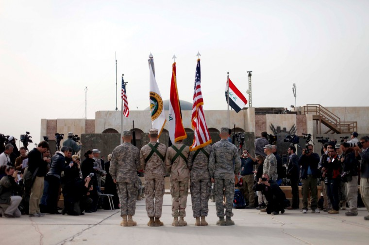 The US flag, Iraq flag, and the US Forces Iraq colors are carried during the flag casing ceremony on December 15, 2011 in Baghdad, Iraq. The ceremony officially marks the end of US military operations in Iraq, all U.S. troops are scheduled to be removed from Iraq by December 31. (Pablo Martinez Monsivais - Pool / Getty Images)