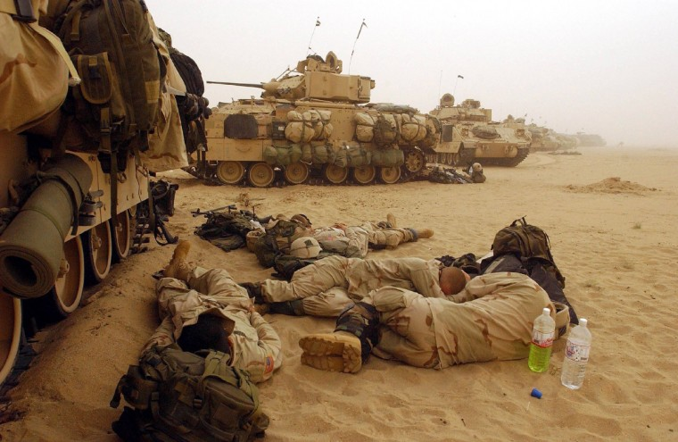 U.S. Army 3rd Division 3-7 infantry soldiers rest near their Bradley fighting vehicles March 19, 2003 during a hold at a forward battle position near the Iraqi border in Kuwait. Iraqi leader Saddam Hussein has rejected U.S. President George W. Bush's call to leave Iraq peacefully setting the stage for an invasion of U.S. and British forces. (Scott Nelson/Getty Images)