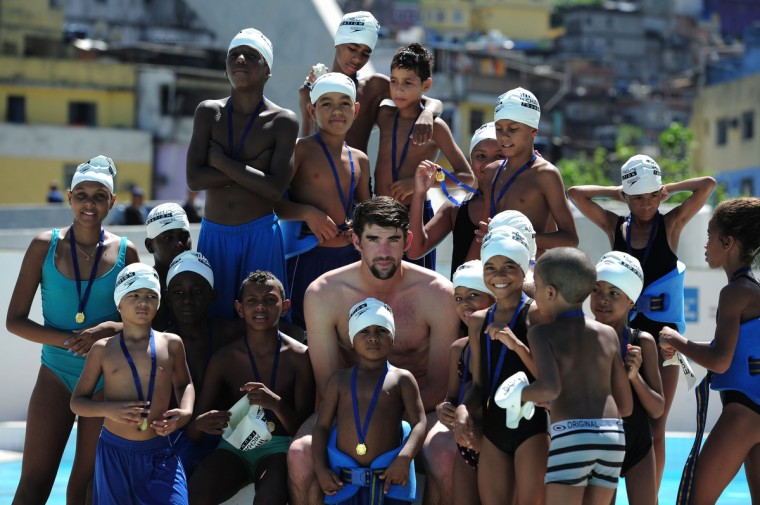 Olympic medalist swimmer Michael Phelps poses with local children at the Laureus visit to Rocinha during the 2013 Laureus World Sports Awards in Rio de Janeiro, Brazil. (Jamie McDonald/Getty Images For Laureus)