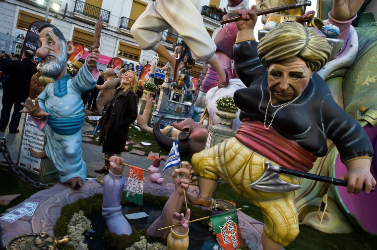 A woman poses next to a Falla depicting German Cancellor Angela Merkel and Spanish Prime Minister Mariano Rajoy in Valencia, Spain. The Fallas festival, which runs from March 15 until March 19, celebrates the arrival of spring with fireworks, fiestas and bonfires made from large ninots (puppets). (David Ramos/Getty Images)