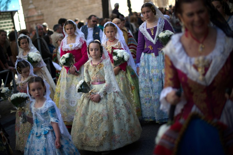 Falleras dressed up in traditonal costume prepare to present flowers to Saint Mary in Valencia, Spain. The Fallas festival, which runs from March 15 until March 19, celebrates the arrival of spring with fireworks, fiestas and bonfires made from large ninots (puppets). (David Ramos/Getty Images)