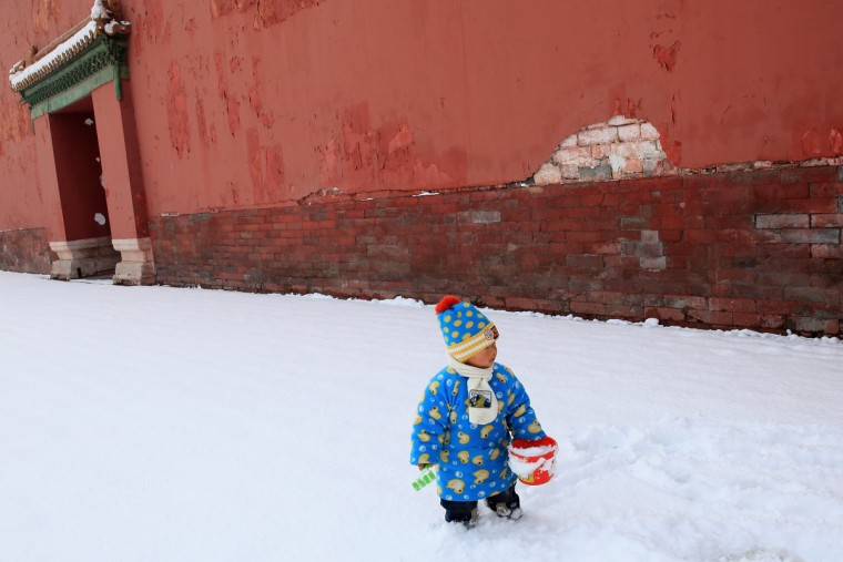 A little boy plays snow at the Imperial Ancestral Temple following overnight snowfall in Beijing, China. Beijing witnessed a heavy spring snowfall with a depth reaching 10-17 centimeters overnight. (Feng Li/Getty Images)