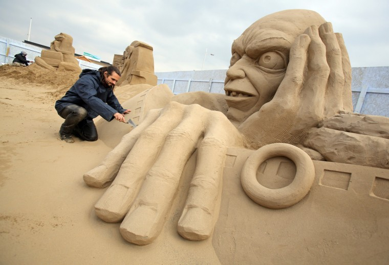 Sand sculptor Radavan Zivny works on a sand sculpture of Gollum. (Matt Cardy/Getty Images)