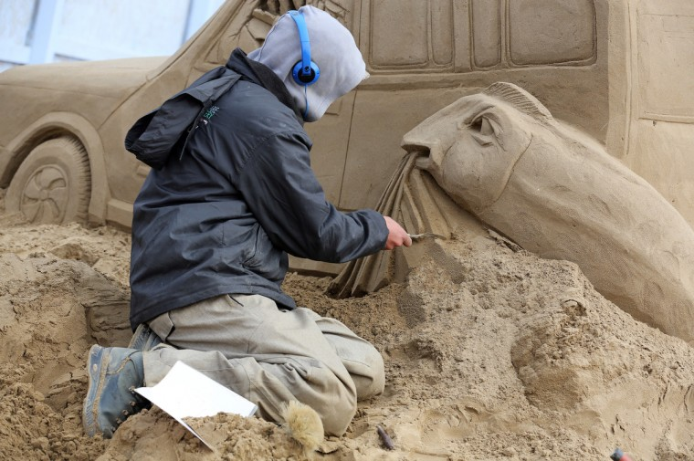 A sand sculptor works on a Jurassic Park themed sand sculpture. (Matt Cardy/Getty Images)