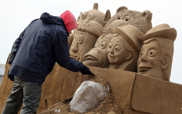 A sand sculptor works on a Toy Story themed sand sculpture. (Matt Cardy/Getty Images)