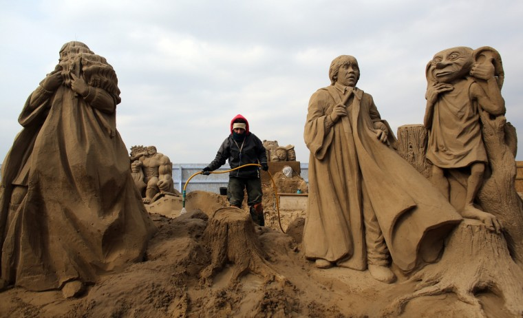 A sand sculptor works on a Harry Potter themed sand sculpture. (Matt Cardy/Getty Images)