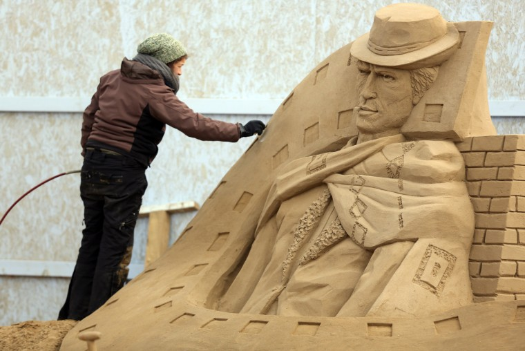 A sand sculptor works on a Clint Eastwood sand sculpture. (Matt Cardy/Getty Images)