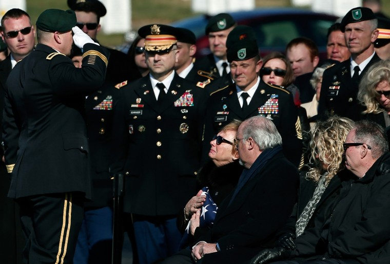 Helen Pederson-Keiser clutches the American flag that covered her son's casket while saluted by Brig. Gen. Christopher K. Haas, commander, U.S. Special Forces Command, during a burial service for her son, U.S. Army Capt. Andrew Pederson-Keel at Arlington National Cemetery in Arlington, Virginia. Capt. Pederson-Keel was killed on March 11, 2013 while serving in Wardak Province, Afghanistan from injuries sustained when attacked by small arms fire from a man in an Afghan police uniform, according to reports. (Win McNamee/Getty Images)