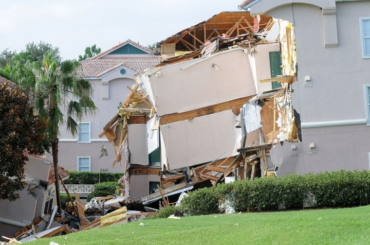 A building sits partially collapsed over a sinkhole at Summer Bay Resort near Disney World in Clermont, Florida. The 40 to 60 foot sinkhole opened up under the resort building reportedly beginning late August 11 into early August 12. There were no injuries or deaths reported. (Gerardo Mora/Getty Images)