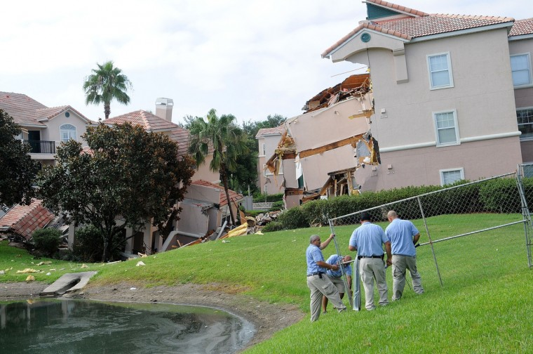 Summer Bay Resort employees install barricades around the collapsed building by a sinkhole at Summer Bay Resort near Walt Disney World on August 12, 2013 in Clermont, Florida. No injuries or victims during the incident. (Gerardo Mora/Getty Images)