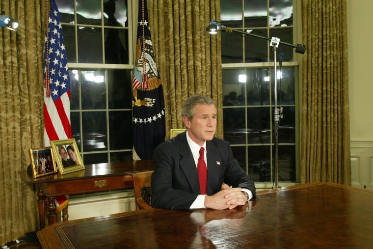 """U.S. President George W. Bush addresses the nation March 19, 2003 in the Oval Office of the White House in Washington, DC. Bush announced that the U.S. military struck at """"targets of opportunity"""" in Iraq March 19, 2003 in Washington, DC. Air defense sirens and anti-aircraft fire was reported briefly in Baghdad. (Alex Wong/Getty Images)"""